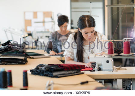 Two seamstresses using sewing machines in workshop - Stock Photo