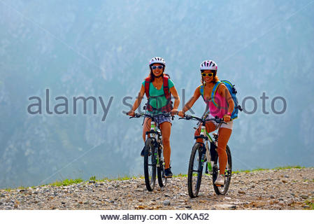 two female mountain bikers on gravel path in the Alps, France, Savoie, Vanoise National Park, Champagny - Stock Photo