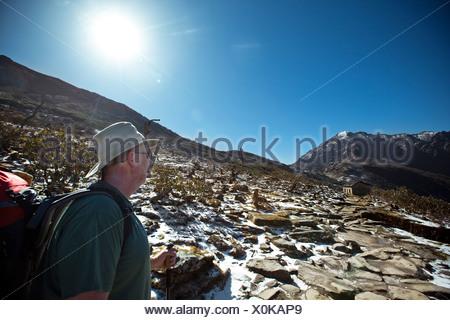 A trekker looks across a high alpine Nepalese pass under the hot sun. - Stock Photo