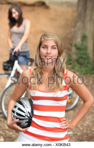 Girls cycling in the forest - Stock Photo