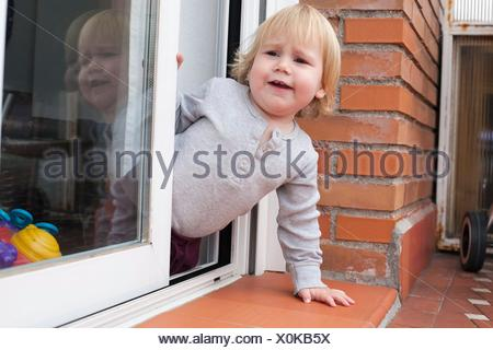 portrait of blonde caucasian baby nineteen month age chubby face calling peering terrace floor supported on the arms. - Stock Photo