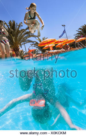 Italy, Sardinia, Alghero, Mother watching children (14-15, 16-17) diving into swimming pool - Stock Photo