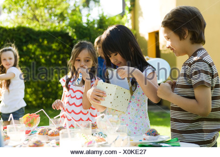 Girl opening gift at birthday party as friends watch - Stock Photo