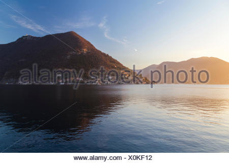 Monte Isola reflection on Lake Iseo during a winter sunset, Brescia Province, Iseo Lake, Lombardy, Italy. - Stock Photo