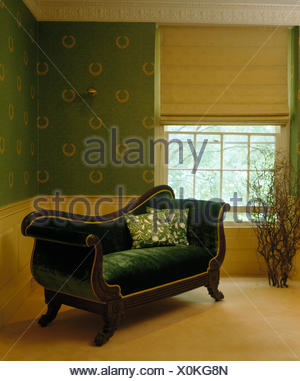 Linen blind on window in country bedroom with French style green velvet sofa and green wallpaper - Stock Photo