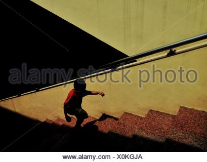 High Angle View Of Boy Moving Up Steps On Sunny Day - Stock Photo