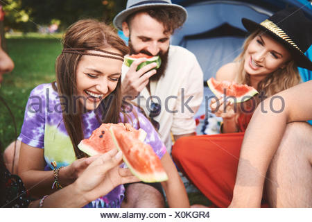 Young boho adult friends eating melon slices at festival - Stock Photo