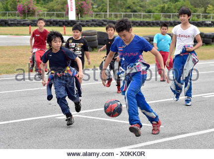 Teenager in racing overalls playing football, Pattaya, Thailand - Stock Photo