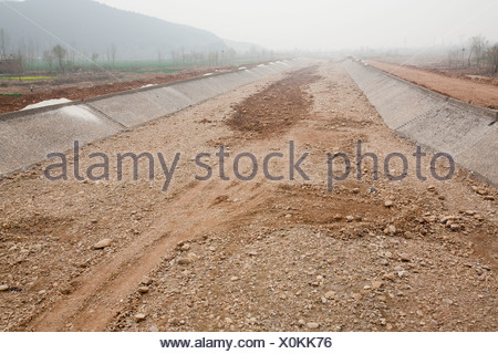 A dry river bed in China caused by global warming induced drought - Stock Photo