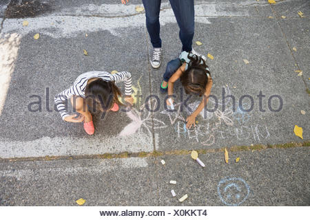 Sisters drawing with sidewalk chalk - Stock Photo