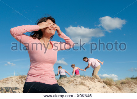 Family playing hide and seek outdoors - Stock Photo