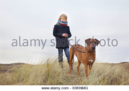 Boy walking his dog in sand dunes at coast - Stock Photo