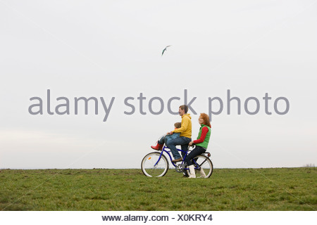 A young family on a bike together - Stock Photo