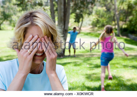 Family playing hide and seek in park girl 8 10 running mother covering eyes in foreground - Stock Photo