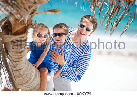 father and two kids sitting on palm trunk at tropical beach, Mexico - Stock Photo