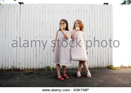 Two girls eating ice lollies - Stock Photo