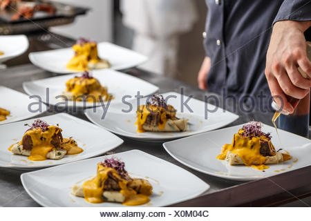 Chef pours sauce on plates - Stock Photo