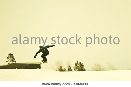 Young male snow boarder mid air on mountain - Stock Photo