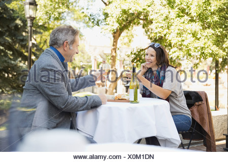 Couple toasting wineglasses at outdoor restaurant - Stock Photo