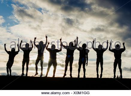 Silhouette of group of young american football players, celebrating - Stock Photo