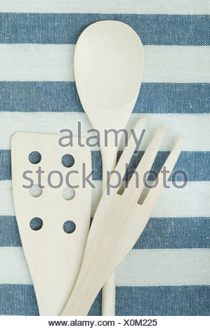 White wooden kitchen utensils on striped tablecloth, close up - Stock Photo