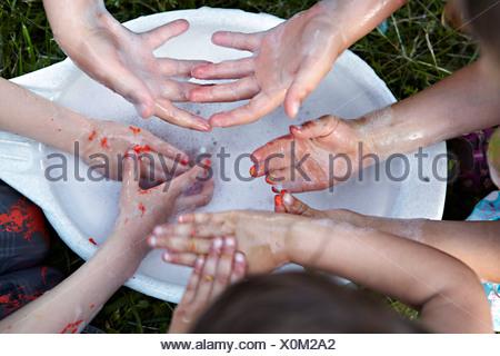 Children washing dirty hands, Munich, Bavaria, Germany - Stock Photo