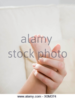 A mother holding her child's foot. - Stock Photo