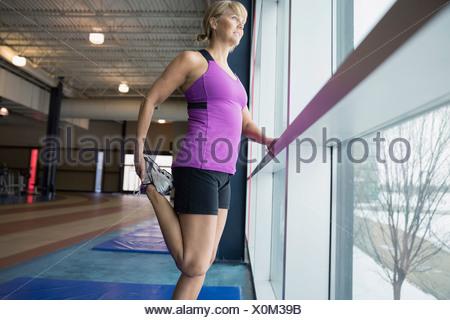 Woman stretching leg at gym window - Stock Photo