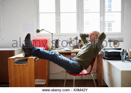 Mature man sitting with feet up at desk - Stock Photo