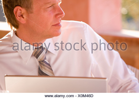 Close up of pensive businessman using laptop - Stock Photo