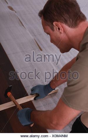 a handyman putting floorboards - Stock Photo