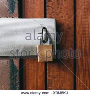 Close up of a wooden doorway with a padlock. - Stock Photo