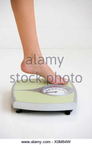 Woman stepping on scale - Stock Photo