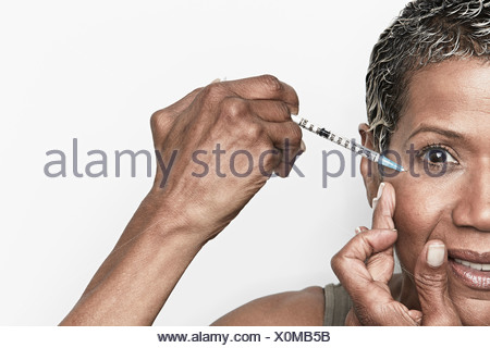 Senior woman injecting herself with botox - Stock Photo