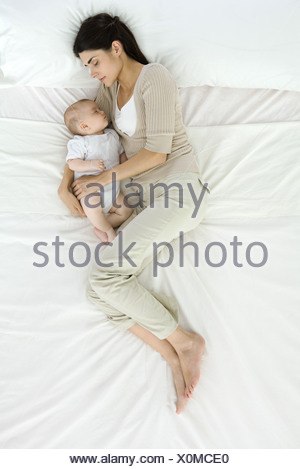 Mother and baby sleeping on bed, overhead view - Stock Photo