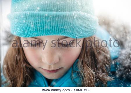Close up portrait of girl wearing knit hat looking down, snowing - Stock Photo