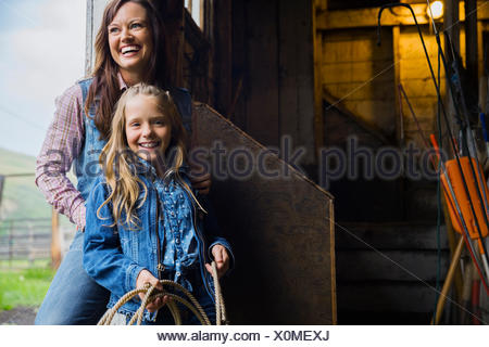 Mother and daughter laughing in barn doorway - Stock Photo