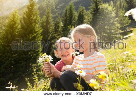 Two young girls in field, picking flowers - Stock Photo