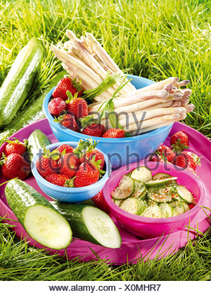 Fruit and vegetables on a tray in the grass - Stock Photo