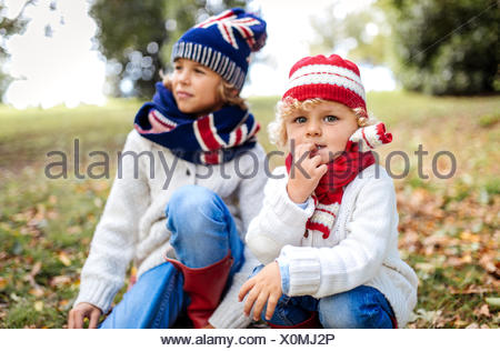 Portrait of blond little boy and his brother in the background  wearing fashionable knit wear in autumn - Stock Photo