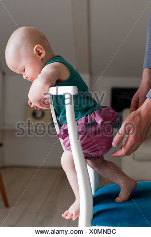 Baby girl standing on chair - Stock Photo