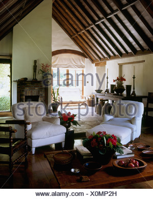White armchairs and low wooden coffee table in country sitting room with a high, vaulted beamed ceiling - Stock Photo