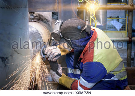 Worker grinding pipe in gas-fired power station - Stock Photo