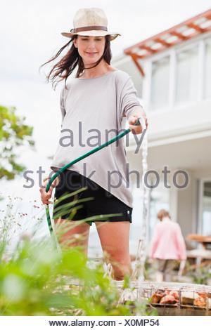 Woman watering plants in backyard - Stock Photo