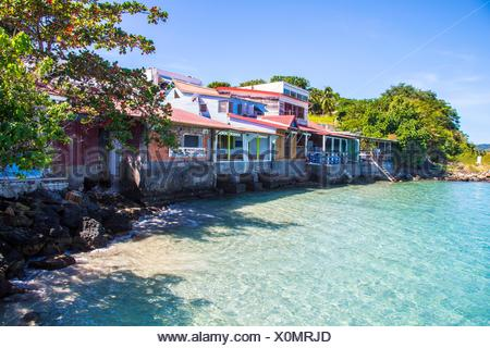 Gorgeous blue sea through transparent water in the South of Martinique, along very colorful pink houses. Caribbean - Stock Photo