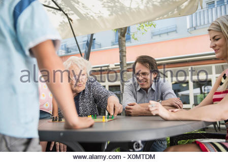 Multi-generation family playing board game - Stock Photo