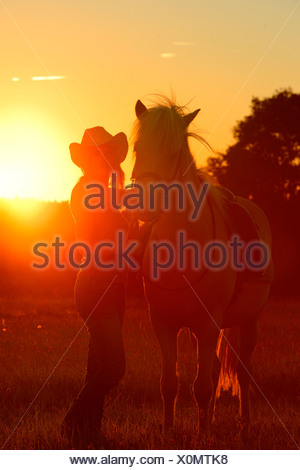 Young woman with horse on meadow in backlight - Stock Photo