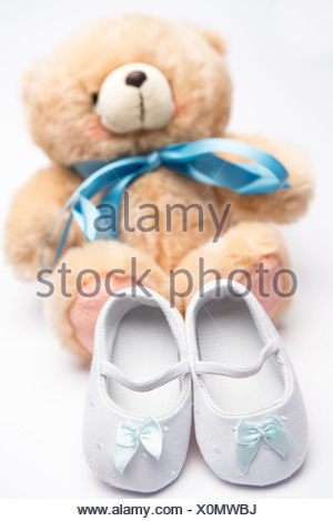 Teddy bear with blue ribbon and white booties - Stock Photo