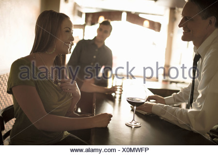 Bartender flirting with young woman in wine bar - Stock Photo