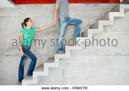 Man leading woman upstairs - Stock Photo
